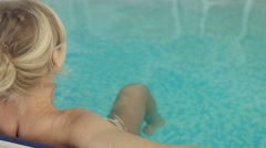 Attractive blonde leaned her back against the edge of the pool Stock Footage