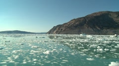 Moving shot sailing through small pieces of ice in calm arctic waters Stock Footage