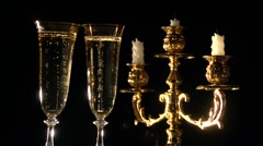 Champagne. Two flutes with champagne by candlelight in a golden candelabrum. - stock footage