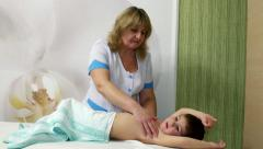 Woman in hospital gown masseur massaging young boy Stock Footage