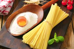Bundle of dried spaghetti, scoop of flour and fresh egg Stock Photos