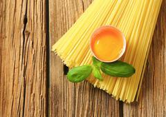 Bundle of spaghetti and raw egg - stock photo