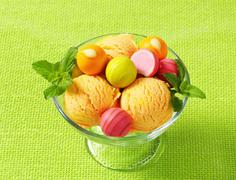 Fruit-flavored ice cream and white chocolate bonbons in a coupe Stock Photos
