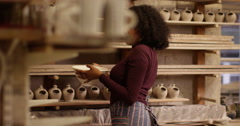 Portrait of a young entrepreneur working in his ceramics store. Slow motion Stock Footage