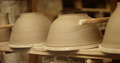 Dolly shot of pottery on shelves at a ceramist's studio. Stock Footage