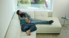 Happy couple cuddling on sofa at home - stock footage