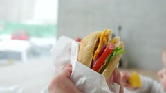 Eating fresh juicy sandwich at a fast food restaurant Stock Footage