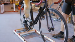 4K Competitive cyclist with prosthetic leg, practicing with trainer in velodrome - stock footage