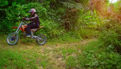 Man riding a dirt bike along a nature trail in Phuket. Stock Footage