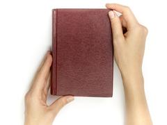 Hands hold blank red hardcover book on white background Stock Photos