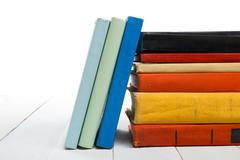 Stack of books at wooden shelf isolated on white background. Back to school Stock Photos