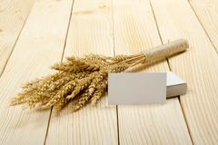 Wheat Ears on Wooden Table with blank business cards. Harvest concept Stock Photos