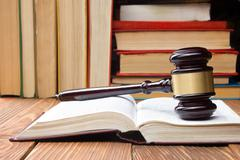 Law book with wooden judges gavel on table in a courtroom or law enforcement - stock photo