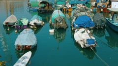 Floating homes of Hong Kong's boat people, moored together in a harbor. Stock Footage