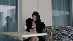 Sexy model in the expensive fur sitting at the table on the balcony in cafe. 4K - stock footage