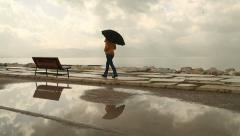 Woman with umbrella walking under the rain Stock Footage