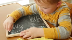 A little boy drawing on his chalkboard in home Stock Footage