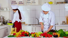 Chef man and woman professional in hat cooking vagetable Stock Footage