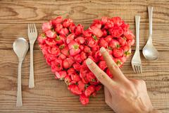 Heart made of red roses in wooden background, covered by an hand to represent Stock Photos