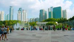 People enjoy near  Lake Symphony fountains in KLCC Park Stock Footage
