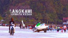 People, water sport equipment and man on motorbike on pantai Cenang beach Stock Footage