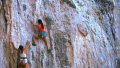 Two female rock climbers slowly climp up the rock with safety belt and ropes Stock Footage