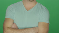 Man crosses his arms and looks tough, on a green screen background Stock Footage