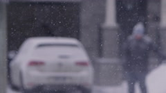 Out of focus man shovelling driveway slow motion snow flakes falling Stock Footage