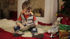 Boy with tablet PC near christmas tree - stock footage