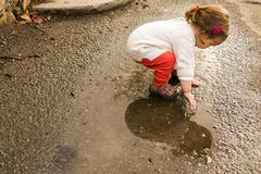 Caucasian baby girl playing in puddle Stock Photos