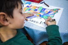 Mixed race boy coloring United States map Stock Photos