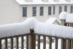 Snow piled high on railing of balcony - stock photo