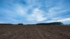 4k timelapse of plowed field landscape with cloudy sky Stock Footage