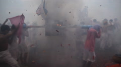 Firecrackers explode over Chinese street procession during festival Stock Footage