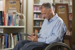 Caucasian man using digital tablet in library - stock photo