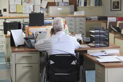Caucasian businessman talking on phone in office Stock Photos