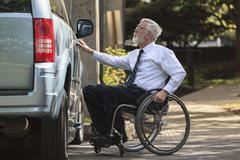 Caucasian businessman in wheelchair opening van door Stock Photos