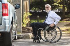 Caucasian businessman in wheelchair at van - stock photo