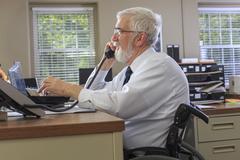 Caucasian businessman talking on phone at desk Stock Photos