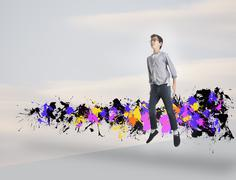 Mixed race boy jumping with paint splatters Stock Photos
