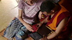 Zoung girl teaching Buddhist Monk how to use tablet - stock footage