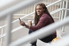 Mixed race man using cell phone on staircase - stock photo