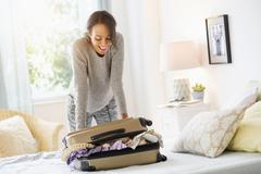 Mixed race woman packing suitcase in bed Stock Photos