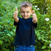 Caucasian boy giving thumbs up in garden Stock Photos