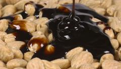 Pouring delicious chocolate syrup over almonds Stock Footage