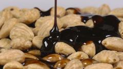 Pouring delicious chocolate syrup over almonds - stock footage