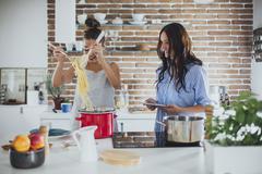 Caucasian women cooking pasta in kitchen Stock Photos