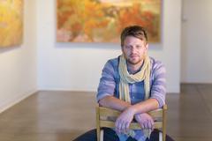 Caucasian man sitting in art gallery Stock Photos