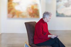 Older mixed race woman using digital tablet in art gallery Stock Photos