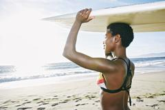 Black woman balancing surfboard on head at beach - stock photo